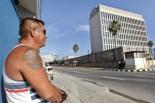 HAB13 LA HABANA (CUBA), 20/07/2015.- Un hombre con un tatuaje de las banderas de estados Unidos y Cuba observa el edificio de la embajada del país norteamericano en la isla hoy, lunes 20 de julio del 2015, en La Habana. Estados Unidos y Cuba escenificaron hoy el restablecimiento de sus relaciones diplomáticas tras casi 55 años de ruptura con la apertura en Washington de la embajada cubana. EFE/Ernesto Mastrascusa